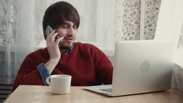 Thumbnail for Young Male Freelancer Chatting on Mobile Phone While Sitting Front Open Laptop Computer Cafe