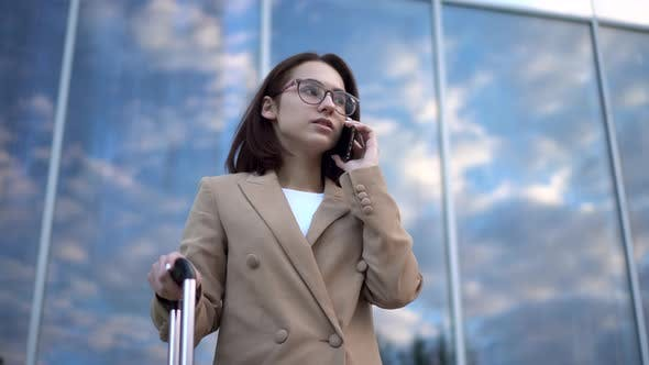Thumbnail for A Young Woman Stands Against the Background of a Business Center and Speaks on the Phone. Girl in a