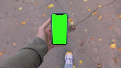 Man walking in park with iPhone 11 in hand. Pre-Keyed green screen ready for your content. POV