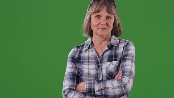 Thumbnail for Somber lady with arms crossed standing in front green chroma key
