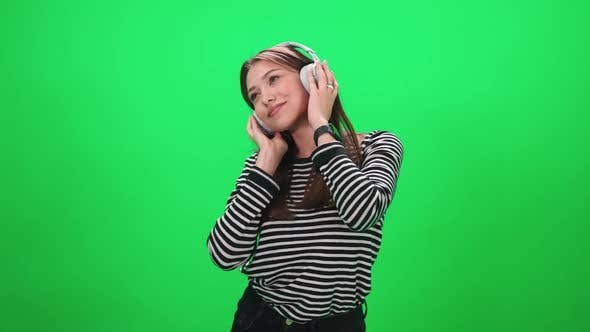 Portrait of a Young Female a Woman Music Lover Listens to Music in Wireless Headphones and Dances