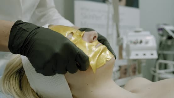 Thumbnail for Cosmetologist Applying Gold Facial Mask To the Face Woman