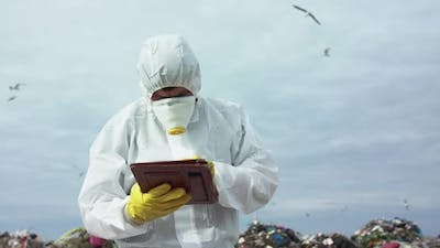 Portrait of Virologist in Protective Costume Noting in Tablet at the Landfill