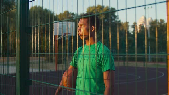 Thumbnail for Smiling Basketball Player on Outdoor Court at Sunrise