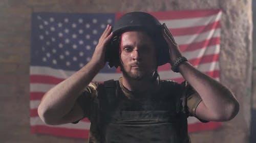 Proud Injured Soldier in Helmet Against US Flag