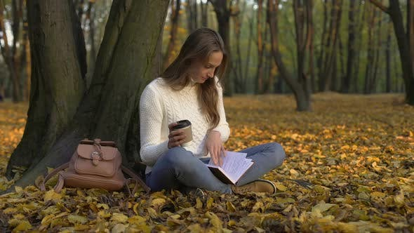 Thumbnail for Cute Girl Sitting Under Tree in Park, Enjoying Coffee and Reading Her Diary