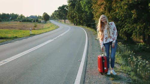 Young Lady Hitchhiking on Countryside Road