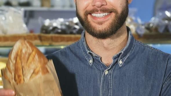 Thumbnail for Cropped close up f ein bärtiger Mann lächelnd hält ein Laib frisches Brot