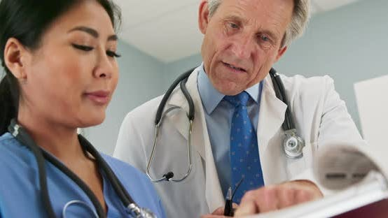 Thumbnail for Male doctor pointing at paperwork while working with female surgeon or nurse
