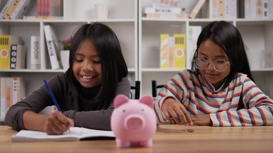 Two girls saving money with pink piggy bank