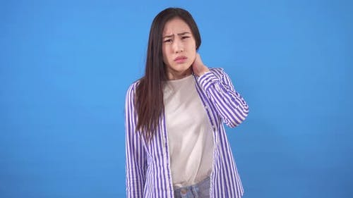 Beautiful Young Asian Woman with Neck Pain Standing on a Blue Background