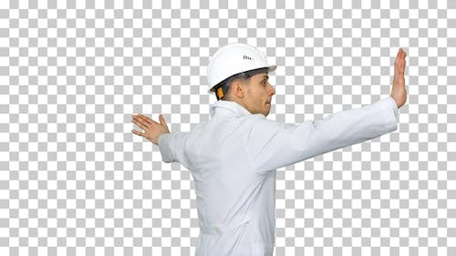 Young workman with helmet in white robe enjoy dancing Alpha
