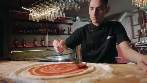 Man Spreading Sauce on Pizza Dough