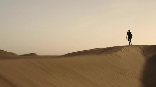 Thumbnail for Man Walking Along Sand Dune In Desert