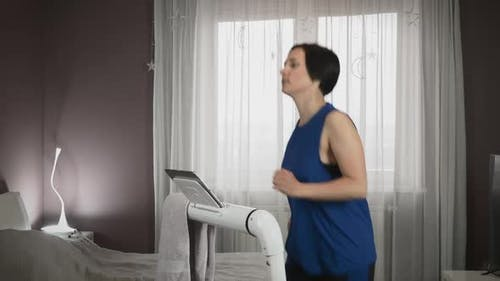 Chubby woman is running on treadmill at home