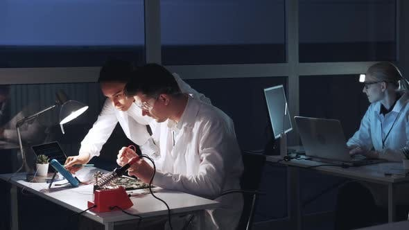 Multiracial Man and Woman Checking Motherboard with Multimeter Tester in Electronics Laboratory