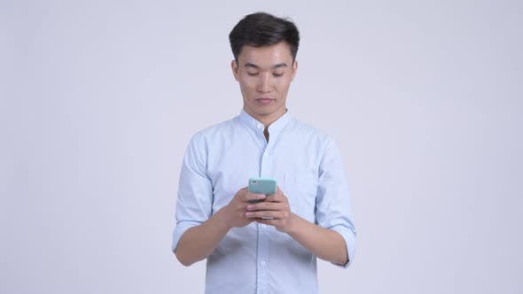 Young Happy Asian Businessman Thinking While Using Phone