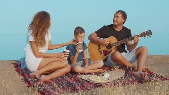 Thumbnail for Family Sitting By the on the Beach in the Evening and Playing Guitar