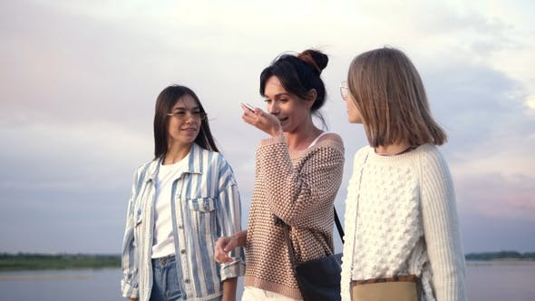 Thumbnail for Three girls walking while one of them recording voice message