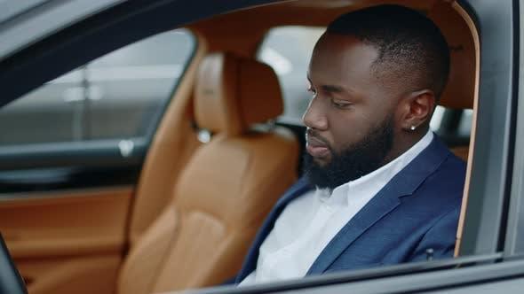 Closeup Businessman Looking at Camera at Car. African Man Smiling in Luxury Car