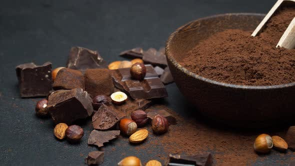 Thumbnail for Dark Chocolate Chunks, Nuts and Cocoa Powder in Wooden Bowl on Dark Concrete Background