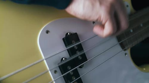 Hand Plays Solo on Metal Strings of White Bass Guitar