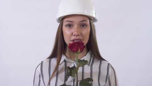 Cover Image for Young Beautiful Woman in Construction Hat Holding a Red Rose in Her Hands and Happy