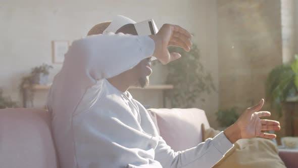 Positiver schwarzer Mann mit VR-Brille zu Hause