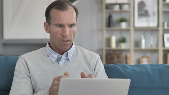 Shocked Middle Aged Man Wondering for Results on Laptop