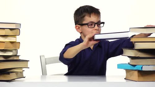 Boy Sits at a Table and Reading a Book. White Background