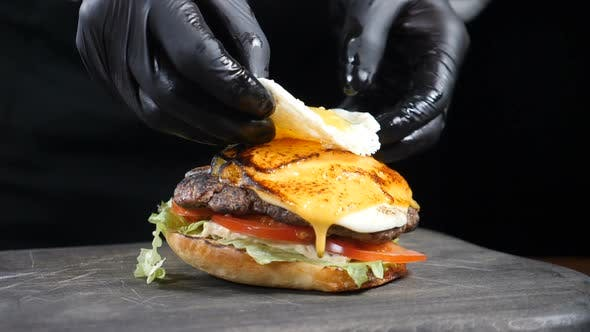 SLOW MOTION FOOD Concept. Chef Making Burger. Close-up. Burger Restaurant Menu Cooking Process. Chef