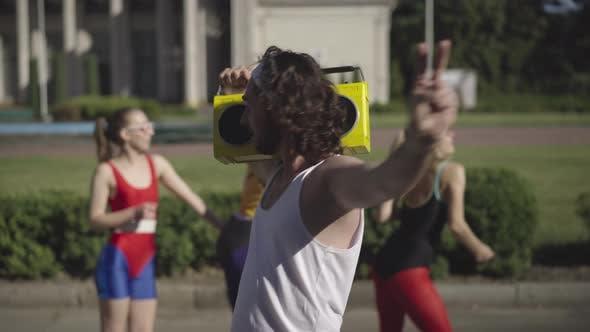 Thumbnail for Middle Shot Porträt eines selbstbewussten Mannes der 1980er Jahre mit gelbem Retro-Tape-Recorder auf der