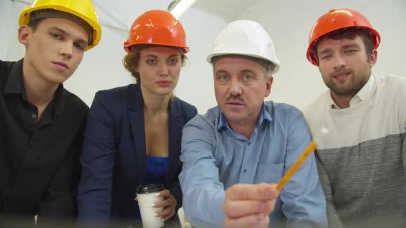 Thumbnail for Architect in Helmet Talks with His Workmates and Shows a Scheme on the Screen of Laptop