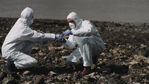 Forensischer Wissenschaftler untersucht Probe am Flussufer