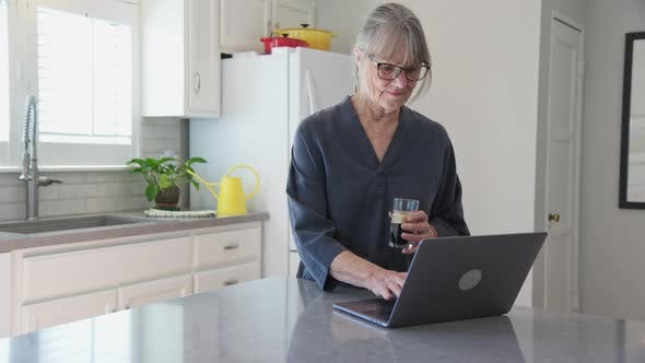 Thumbnail for Senior white woman using laptop computer in kitchen while drinking iced coffee