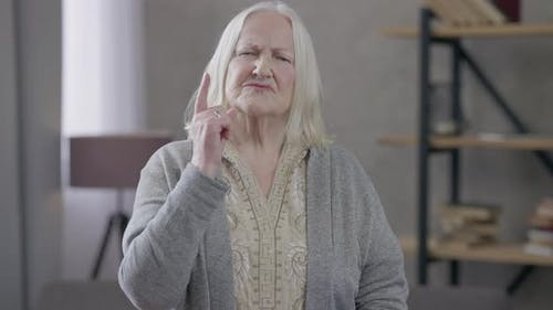 Medium Shot of Dissatisfied Old Caucasian Woman Scolding Showing Finger Looking at Camera