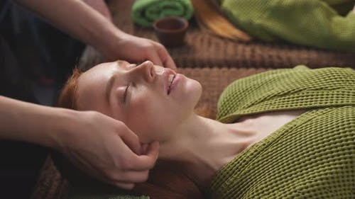 Woman Enjoys a Relaxing Facial Massage at a Beauty Salon