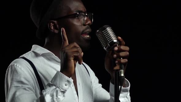 Thumbnail for Singer Sings Into a Retro Microphone and Dancing Near It. Black Background. Slow Motion. Close Up