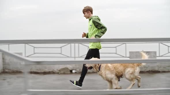 Thumbnail for Sporty Teenage Boy Jogging with Labrador Dog