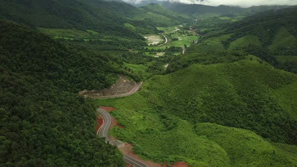Aerial View of Countryside Road passing through the Mountain Landscape