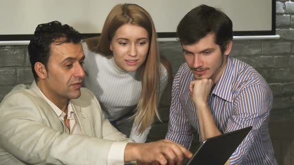 Cover Image for Group of Business People Discussing Something on the Laptop During the Meeting
