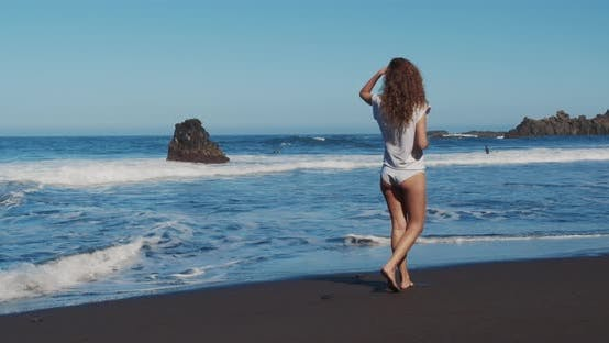 Girl Walking Along the Ocean. Back View of a Young Caucasian Woman on a Beach and Looking Out To