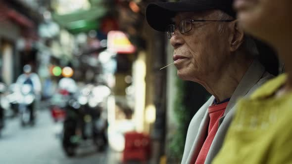 Thumbnail for Handheld view of Vietnamese senior man in the street. Shot with RED helium camera in 8K