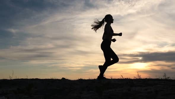 Young Lady Running on Seashore at Sunset