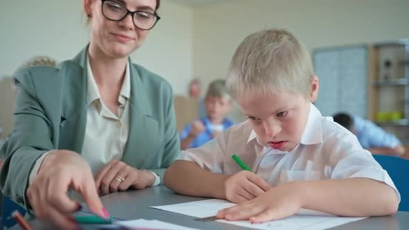 Pedagogue Works with Down Syndrome Boy Young Woman in Glasses Teaches the Pupil Sitting at Desk at