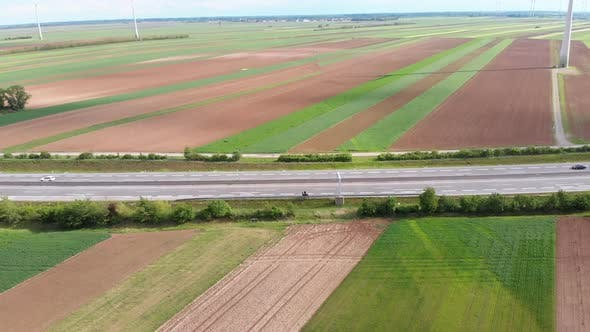 Thumbnail for Traveler Standing on a Motorcycle on Highway, Takes Off a Drone Near Wind Farms, Austria