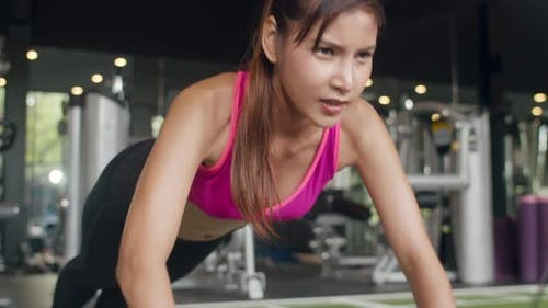 Beautiful young athlete Asian lady exercise doing push-ups fat burning workout in fitness class.