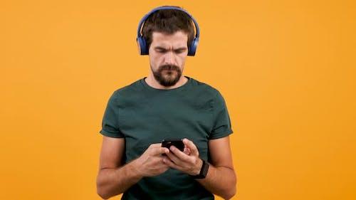 Handsome Man Puts Blue Headphones on Head, Start Listening Music and Nodding