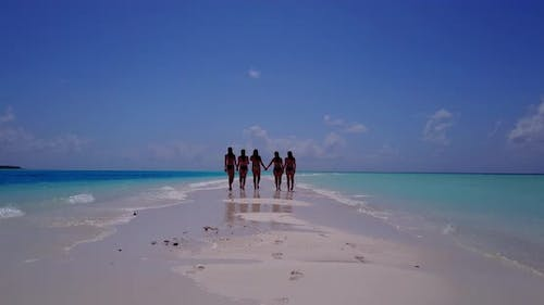 Modern happy ladies on holiday enjoying life at the beach on sunny blue and white sand background 4K
