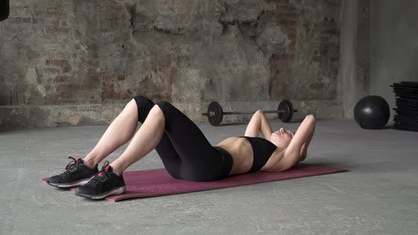 Young sporty girl doing exercises for press practicing fitness and yoga full shot